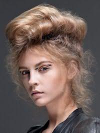 Прическа ракушка для вьющихся волос поможет создать креативный образ. Влажные пряди необходимо высушить феном по направлению наверх. Затем они оформляются в два объемных валика на макушке. Волоки на висках и затылке остаются свободными.