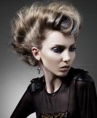 Очень стильный образ поможет создать объемная прическа ракушка. Длинные волосы пепельного оттенка начесываются по всей длине и собираются в валик по всей голове, начиная от макушки и заканчивая затылком. Особый шарм добавят колорированные пряди синего цвета.
