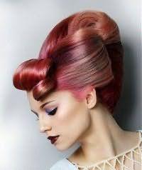 Очень элегантная сложная высокая прическа ракушка гармонирует с розовым цветом волос. Длинная челка завивается назад в ретро стиле. Пряди с висков гладко зачесываются и отделяются от основной массы волос, которая начесывается и собирается в классический вертикальный валик.