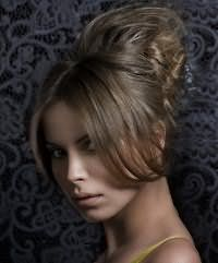 Элегантная прическа ракушка. Удлиненная челка делится на ровный пробор и укладывается по бокам. Волосы накручиваются в легкие волны, начесываются на макушке и собираются в высокую ракушку.