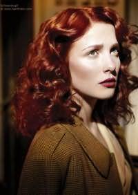 Элегантная прическа 40-х годов на длинные волосы восхищает своей женственностью. Пряди делятся на боковой пробор и укладываются в кудри при помощи бигуди. Зафиксирует прическу лак для волос.