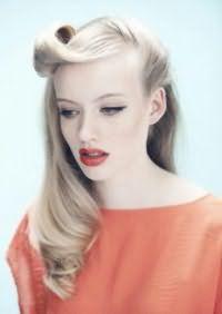 Данная модель прически 40-х годов великолепно подчеркивает красоту светлых волос. Длинные пряди выпрямляются при помощи утюжка, концы укладываются в локоны, челка закручивается в валик и фиксируется по направлению ото лба.