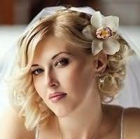 Свадебная прическа с челкой для кудрявых волос с цветами.