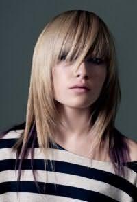 Дерзкая стрижка на светлые средние волосы тонкого типа, выполненная в технике лесенка, гармонично дополняется прямой челкой длиной ниже линии бровей и мелированными прядями фиолетового цвета