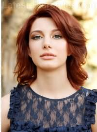 Стрижка лесенка на средние волосы густого типа рыжего оттенка будет элегантно смотреться с укладкой в виде крупных локонов, дополненных удлиненной челкой на бок