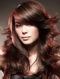 Вариант долговременной укладки длинных или средних волос в хаотичном виде прекрасно смотрится с объемной косой челкой и колорированными прядями