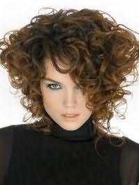 Кудрявые густые волосы средней длины интересно смотрятся в асимметричном варианте стрижки с удлиненными прядями, напоминающими стиль 80-х годов