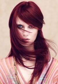 Стрижка каскад с косой челкой на длинные волосы темно-красного цвета стильно смотрится в тандеме с дневным макияжем для голубых глаз и светлой кожи