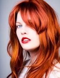 Эффектный огненно-рыжий цвет волос, оформленных в виде средней стрижки каскад с косой челкой, изумительно дополняет макияж для голубых глаз с акцентом на губы