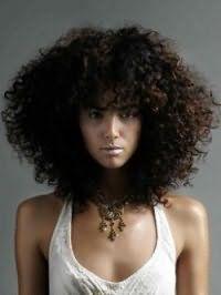 Девушкам со смуглой кожей и черным цветом волос подойдет удлиненная стрижка с челкой на кудрявые волосы густого типа, напоминающая афро завитки и химическую завивку