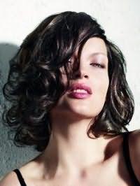 Вариант стрижки для вьющихся волос средней длины черного цвета
