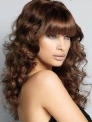 Карамельный цвет волос гармонично выглядит на густых локонах волнистого типа с выпрямленной челкой и дополняется легким дневным макияжем для карих глаз