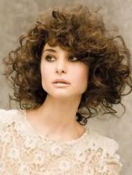 Густые и непослушные кудрявые волосы легко преображаются в стрижке средней длины, а объемная челка на бок поможет скорректировать квадратную форму лица