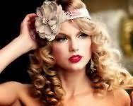 Роскошный вечерний образ, состоящий из прически с повязкой, украшенной цветком бежевого оттенка, на распущенных волосах, уложенных в мелкие кудри и макияжа губ в ярко-красном тоне